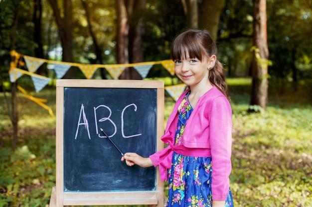 黒板の近くで小さな女の子が勉強しています。学校に戻る。教育、学校のコンセプト