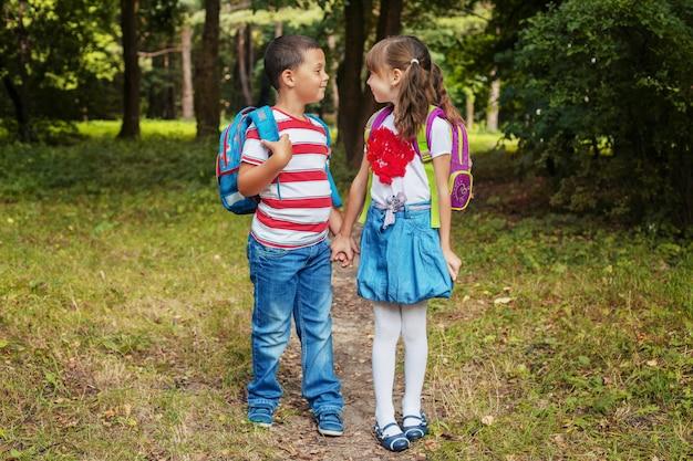 バックパックの子供たち。男の子と女の子は友達です。学校に戻る。教育の概念、学校、