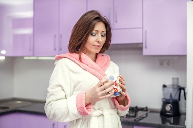 彼女のキッチンでコーヒーを飲みながらバスローブの若い女性