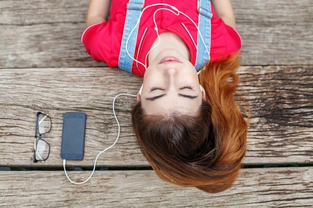 若い女の子が桟橋に横になり、ヘッドフォンでオーディオブックを聞きます。ライフスタイル、旅行、音楽、休息の概念。