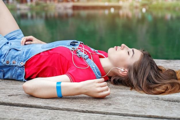 若い女の子が桟橋に横になっていて、ヘッドフォンを聞きます。ライフスタイル、旅行、音楽、休息の概念。
