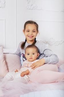 Счастливые дети, две сестры сидят на кровати. концепция детства и воспитания.