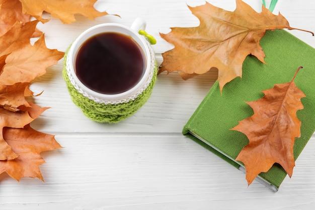 一杯のコーヒーと本。秋、静物、リラクゼーション、研究の概念