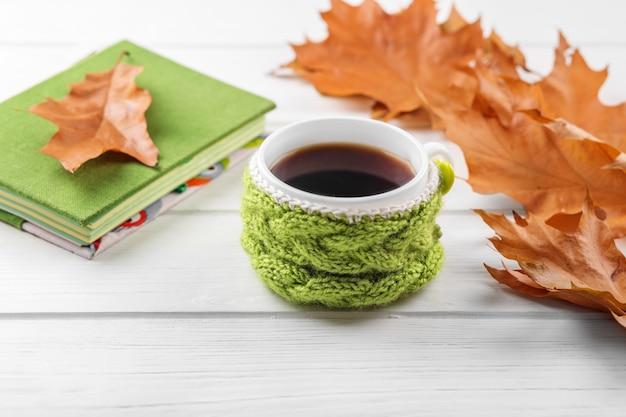 一杯のコーヒーとノート。秋、静物、リラクゼーション、研究の概念
