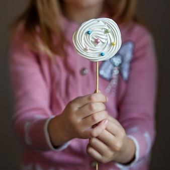 子供の手に棒のキャンディ。お菓子、パーティー、ベーカリーの概念。