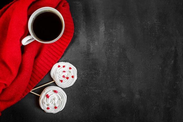 強いホットコーヒーと赤の背景にフランスのメレンゲ。飲み物、レジャー、ライフスタイルの概念。