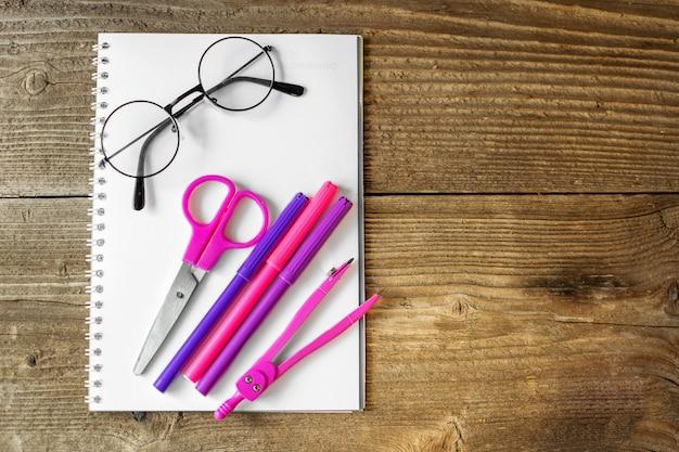 ピンクのはさみ、メモ帳、マーカー。