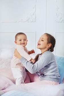 Старшая сестра играет с ребенком в комнате. детство и образование