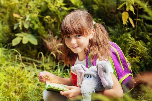 Маленькая школьница читает книгу. ребенок с рюкзаком. обратно в школу. образование, школа, детство