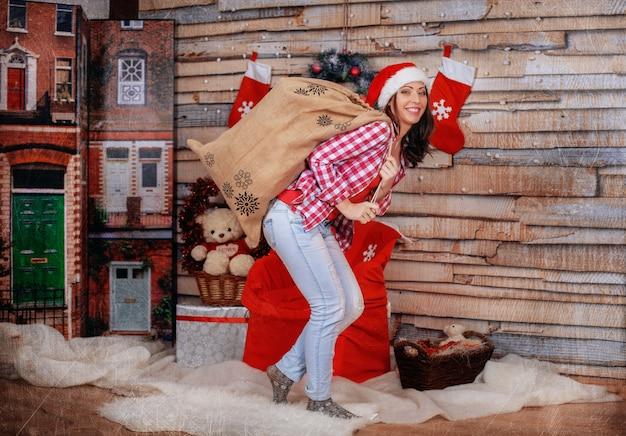 贈り物の袋を運ぶ面白い女の子。