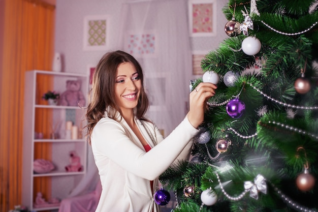若い幸せな女は、クリスマスツリーを飾る。