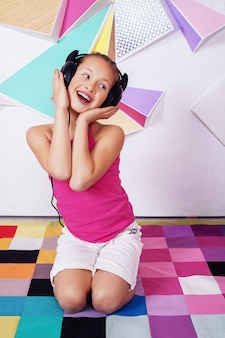 音楽を聴くと歌う美しい幸せな子供の女の子。