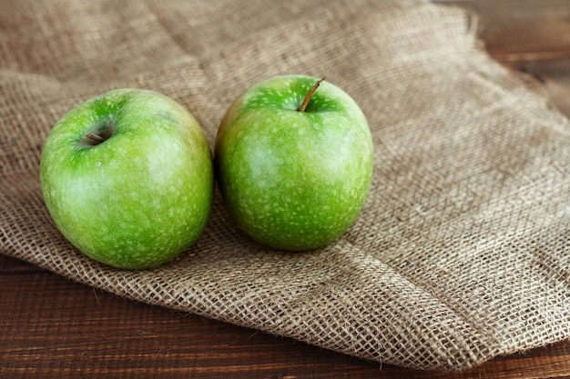 Две зеленые яблоки на мешок на столе