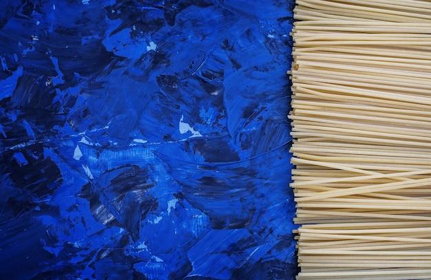 スパゲッティと青色の背景。