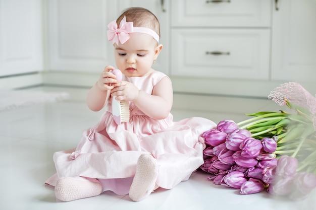 Маленький ребенок держит расческу.