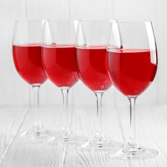 Много бокалов бордового французского вина на деревянном столе