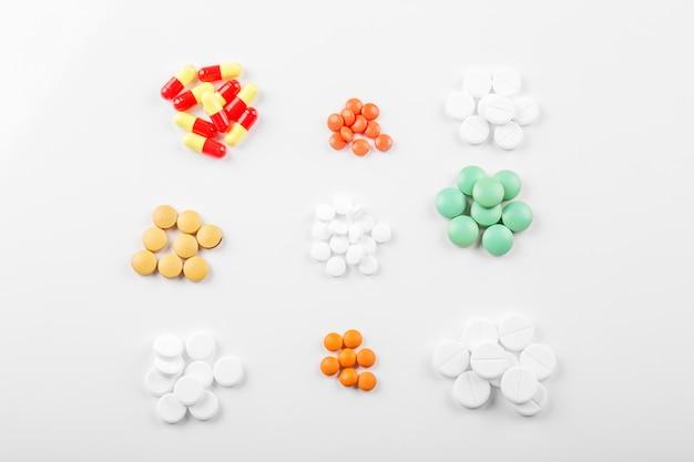 Разные таблетки на белой поверхности
