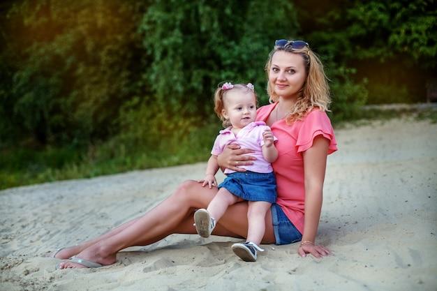 Мама и маленькая дочь отдыха на пляже. концепция детства, путешествий и образа жизни.