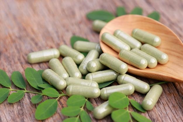 多くのハーブからの健康的な食事のためのカプセルが付いている漢方薬の粉、よい生活のための代替サプリメント