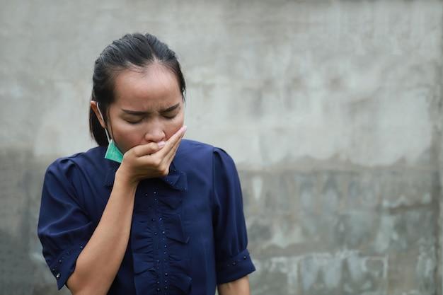 Защитная маска азиатской девушки нося с чувством холода лихорадки для концепции вируса короны