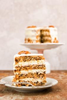 クリームチーズのフロスティングとニンジンとクルミのケーキ。スライスとケーキをバックグラウンドで。