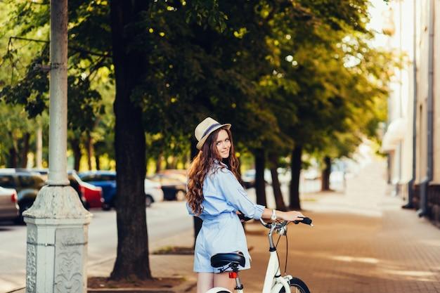 自転車で帽子のスタイリッシュな女の子
