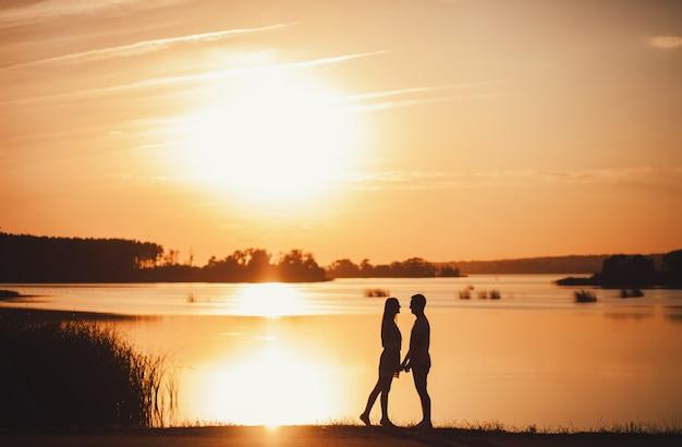 ロマンチックなカップルは夕暮れ時立っています。コピースペース