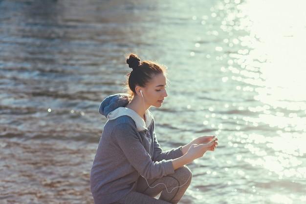 女性ランナーは休憩して音楽を聴いています