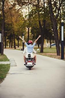 スクーターに乗って美しい若いカップル