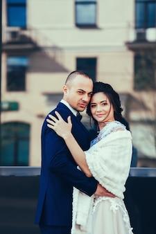Жених и невеста обнимаются в городе