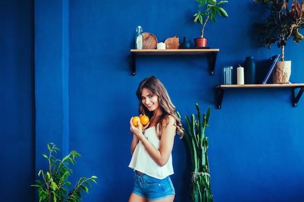 部屋でオレンジを持つ女性