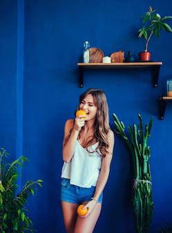 美容モデルの女の子はジューシーオレンジを取る