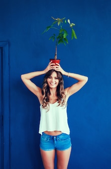 Женщина, держащая растения на голове.