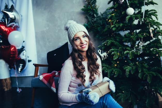 帽子の幸せな若い女性は贈り物を保持します