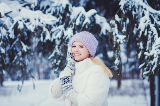 彼女の顔を手で雪の中で女性