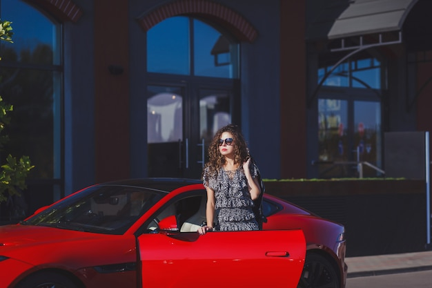 都市の赤い車の近くの女性