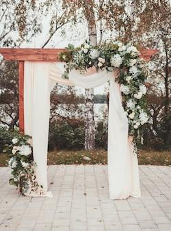 Свадебная арка украшена тканью и цветами