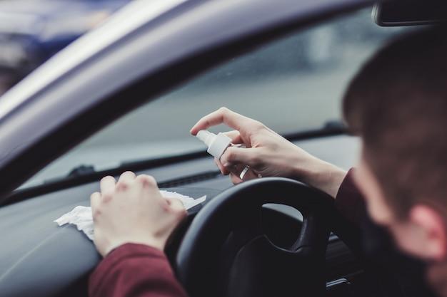 ドライバーが車の表面を消毒する