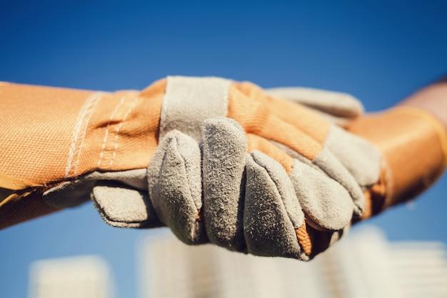 ビルダーはお互いに挨拶する手袋で手を