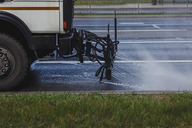 機械が都市のアスファルト道路を洗う