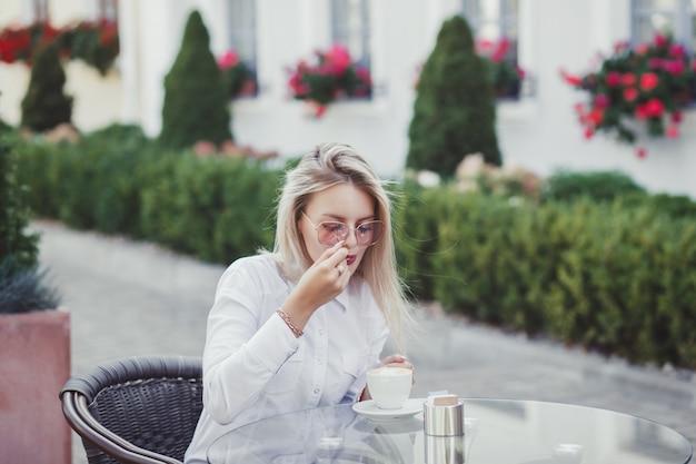 Женщина в кафе сидит за столом