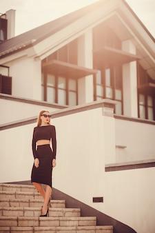 Офисная женщина одета в строгую черную юбку-карандаш и топ