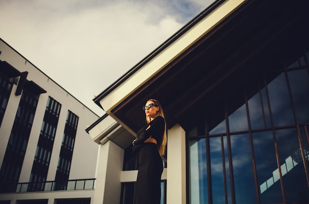 Привлекательная модель в очках стоит возле бизнес-центра