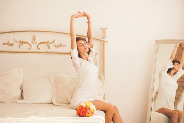 女性がベッドの上に座ってストレッチ