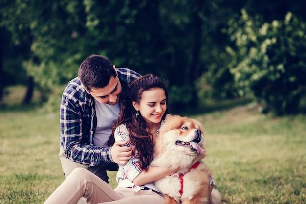 美しい若いカップルと犬