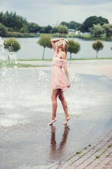Женщина модель позирует в платье возле фонтана