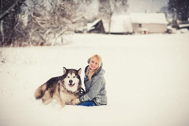 Милая женщина в свитере сидит с собакой