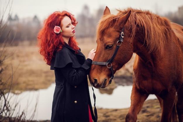 Рыжая девушка гладит лошадь.