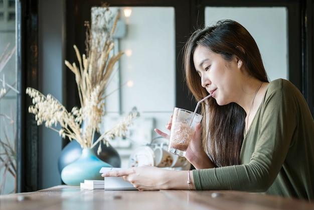 本を読んで、コーヒーショップの木製のカウンターでアイスチョコレートを飲むアジアの女性のクローズアップ