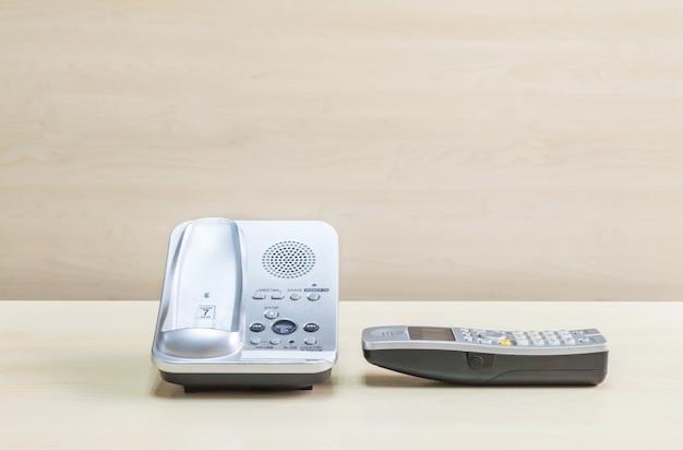 灰色のクローズアップ電話、ぼやけた木製の机の上のオフィスの電話